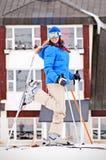 Mulher no esqui com o hotel no fundo Fotografia de Stock Royalty Free