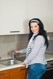 Mulher no faucet aberto da cozinha Fotos de Stock