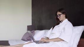 Mulher no funcionamento branco no portátil, assento do roupão e de vidros na cama Sorriso e trabalho fêmeas no computador Negócio vídeos de arquivo