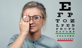 Mulher no fundo da carta de teste do olho, conceito do cuidado do olho fotos de stock