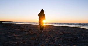 A mulher no fundo do por do sol o sol no litoral faz exercícios vídeos de arquivo