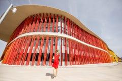 Mulher no fundo vermelho da parede Foto de Stock