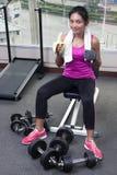 Mulher no gym que come uma banana Foto de Stock