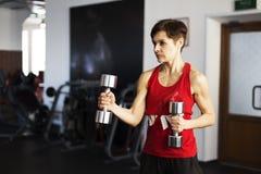 Mulher no gym que faz exercícios com pesos fotografia de stock