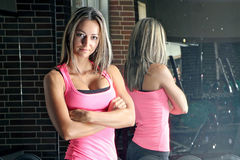 Mulher no gym sobre com ela de volta a um espelho Fotos de Stock Royalty Free