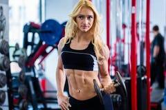 Mulher no halterofilismo que levanta peso no gym Fotografia de Stock