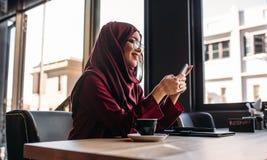 Mulher no hijab que senta-se no café usando o telefone celular imagens de stock