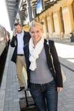 Mulher no homem do estação de caminhos-de-ferro no telemóvel fotografia de stock royalty free