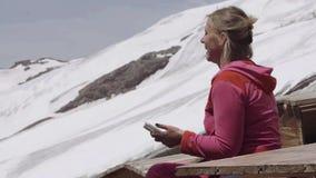 Mulher no hoodie cor-de-rosa com sigarette e no smartphone que ri do acampamento da montanha vídeos de arquivo