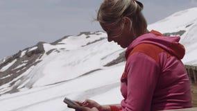 Mulher no hoodie cor-de-rosa que texting no smartphone no acampamento da montanha vídeos de arquivo