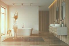 Mulher no interior branco e de madeira do banheiro imagem de stock