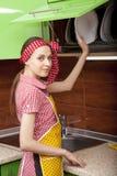 Mulher no interior da cozinha com placas limpas Fotografia de Stock Royalty Free