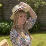 Mulher no jardim que põe sobre um chapéu de palha imagem de stock royalty free