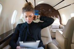 Mulher no jato incorporado que looging no tablet pc Imagem de Stock