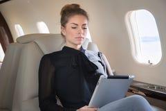 Mulher no jato incorporado que looging no tablet pc Imagens de Stock Royalty Free