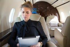 Mulher no jato incorporado que looging no tablet pc Fotografia de Stock Royalty Free