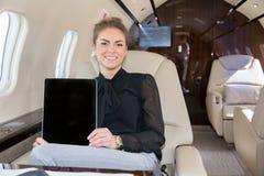 Mulher no jato incorporado que mostra o tablet pc imagem de stock