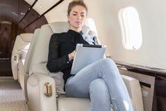 Mulher no jato incorporado que olha o tablet pc Foto de Stock