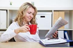 Mulher no jornal da leitura do escritório foto de stock royalty free