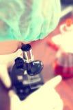 Mulher no laboratório de química com microscópio fotos de stock royalty free