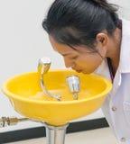 A mulher no laboratório usa os olhos da arruela Foto de Stock