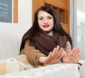 Mulher no lenço que aquece-se perto do calefator morno Imagens de Stock