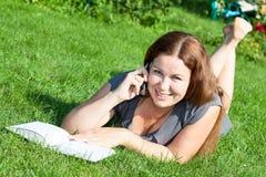 Mulher no livro de leitura da grama verde e discurso no telefone Imagem de Stock