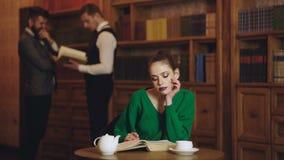 Mulher no livro lido biblioteca e no café bebendo do copo Café da literatura com menina bonito e homens no fundo estudante video estoque