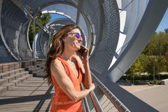 Mulher no lugar urbano moderno que fala no móbil imagens de stock