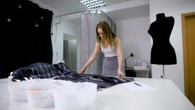 Mulher no material do corte da loja do alfaiate para criar a roupa nova video estoque