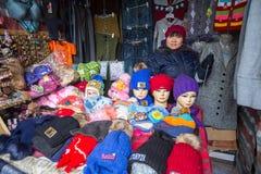 A mulher no mercado da cidade vende chapéus do inverno Em Bayan-Olgiy a província é povoada a 88,7% por Kazakhs Foto de Stock Royalty Free