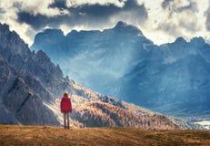 A mulher no monte está olhando nas montanhas majestosas no por do sol foto de stock