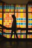 Mulher no movimento perto do vidro colorido fotos de stock royalty free