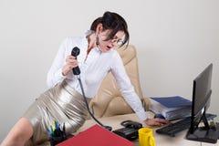 Mulher no olhar da mesa em um telefone de chamada Imagem de Stock Royalty Free