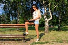 Mulher no parque com caderno Fotografia de Stock Royalty Free