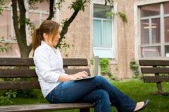 Mulher no parque com seu computador Imagem de Stock