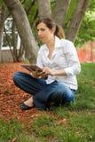 Mulher no parque com tabuleta móvel Fotos de Stock Royalty Free