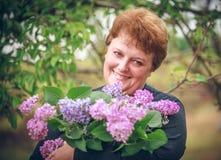 Mulher no parque com um ramalhete grande de um lilás Fotografia de Stock