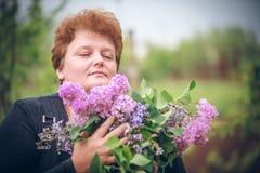 Mulher no parque com um ramalhete grande de um lilás Fotos de Stock Royalty Free