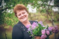 Mulher no parque com um ramalhete grande de um lilás Imagens de Stock Royalty Free