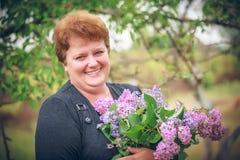 Mulher no parque com um ramalhete grande de um lilás Fotos de Stock