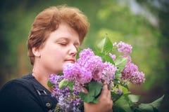 Mulher no parque com um ramalhete grande de um lilás Foto de Stock Royalty Free