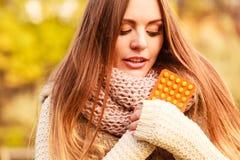 Mulher no parque do outono que guarda medicinas das vitaminas Foto de Stock