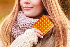 Mulher no parque do outono que guarda medicinas das vitaminas imagem de stock