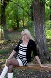 A mulher no parque em um banco na perspectiva do w imagens de stock