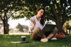 Mulher no parque que manda uma videoconferência chamar seu portátil imagem de stock