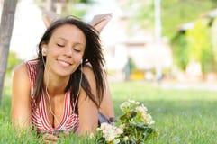 A mulher no parque verde, música e relaxa Fotografia de Stock Royalty Free