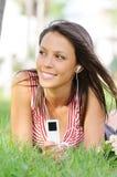 A mulher no parque verde, música e relaxa Imagem de Stock