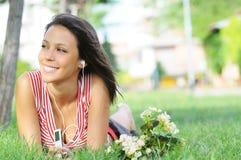A mulher no parque verde, música e relaxa Fotografia de Stock