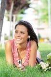 A mulher no parque verde, música e relaxa Imagens de Stock